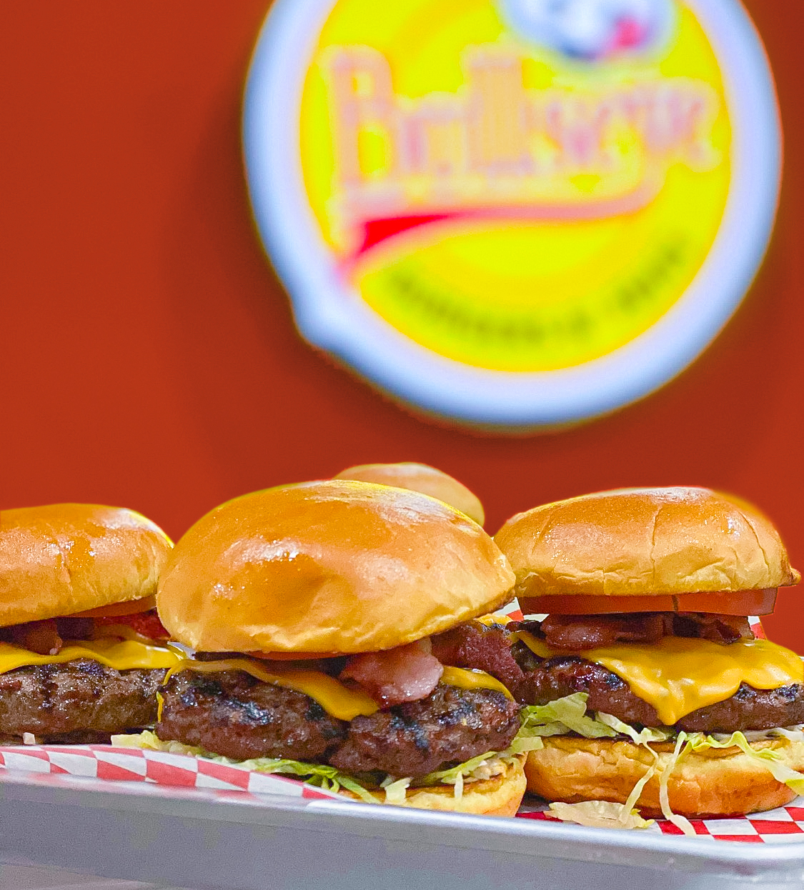 Platter of four Bullseye Burgers with bacon, cheese, lettuce, and tomato